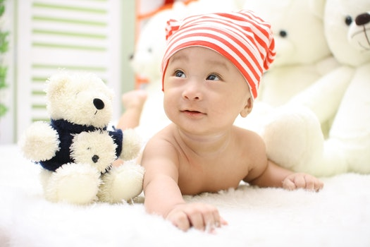 Smiling Toddler Wearing Orange and White Knit Cap Beside Black and White Bear Plush Toy