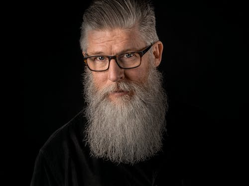 Serious bearded gray haired man looking at camera