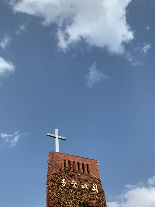 From below of ancient red brick tower with christian cross on top against blue cloudy sky