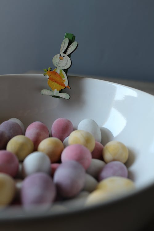 Bowl with multicolored Easter eggs and bunny pin