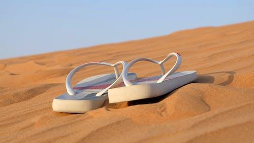Foto profissional grátis de areia, borracha, chinelo, chinelos
