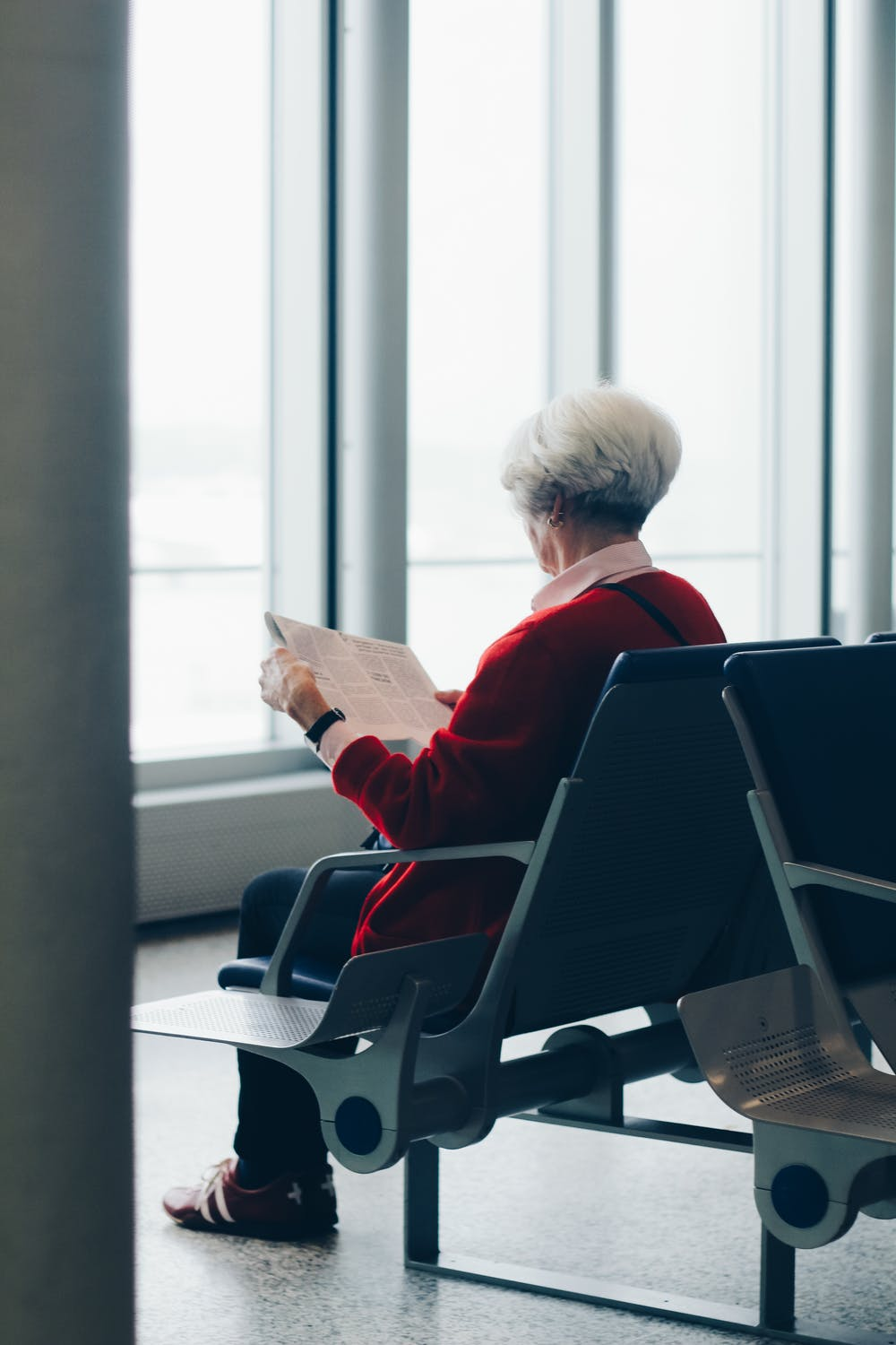 Old woman sitting on a chair while reading the newspaper. | Photo: Pexels