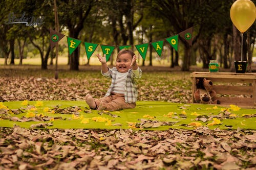 Baby Sitting on Green Textile with Dry Leaves