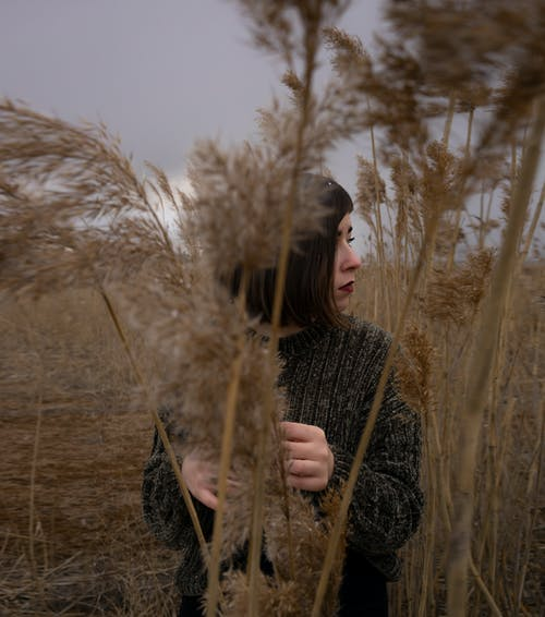 Woman in Black Sweater Standing on Brown Grass Field