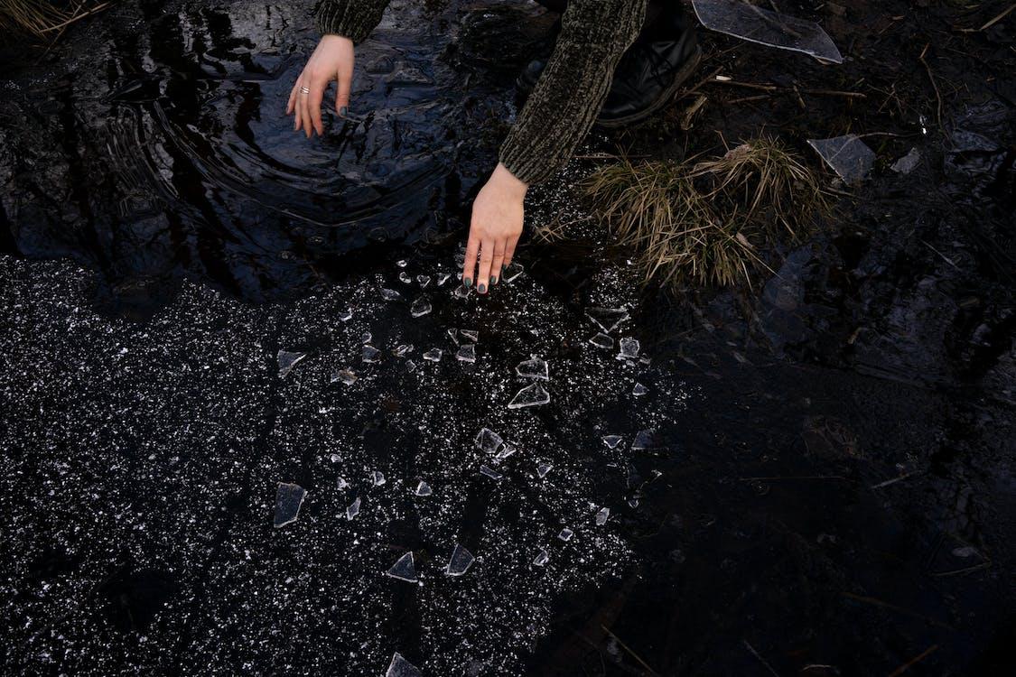 Crop woman picking up broken glass near lake in countryside