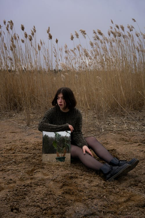 Woman in Black Shirt Sitting on Brown Sand Near Body of Water