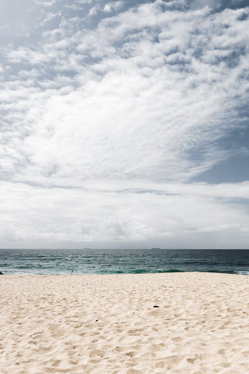 White Sand Beach Under White Clouds and Blue Sky