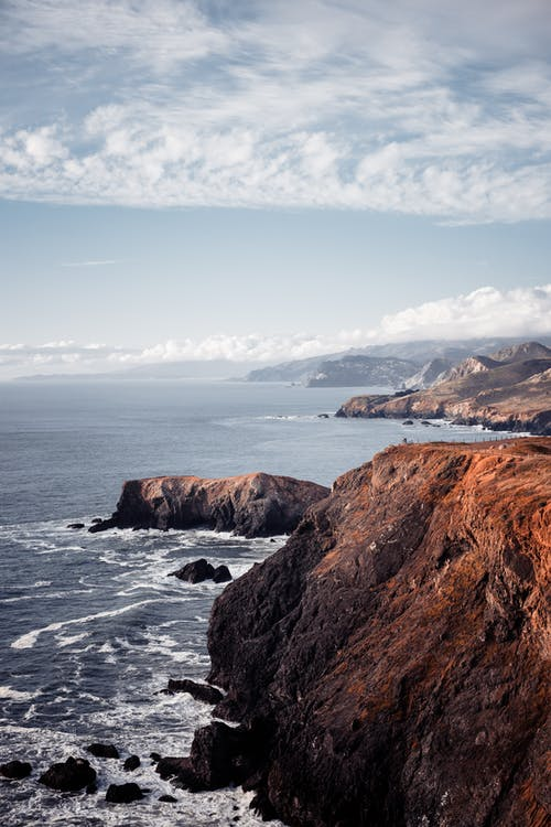 Brown Rock Formation on Sea Under Blue Sky