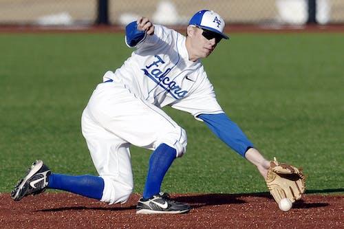 Man Wearing Blue and White Falcons Baseball Jersey Shirt With Brown Baseball Gloves Catching White Baseball