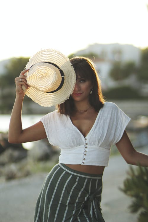 Woman in White Shirt and Blue and White Striped Skirt Wearing Brown Straw Hat