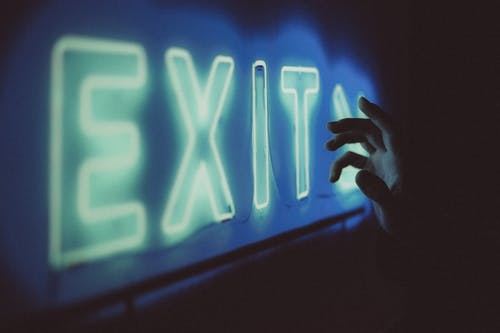 Crop faceless person standing in dark room near bright blue neon light sign with exit inscription