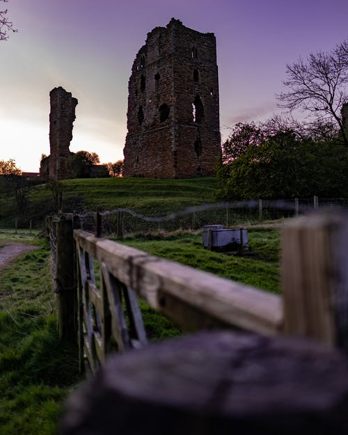 Low angle of old shabby damaged building made of red bricks  located on green grassy hill in countryside against purple sunset sky