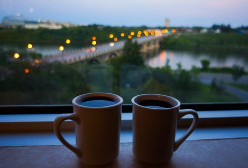 Cups of Black Coffee on the Window Sill