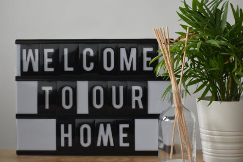 Potted plant and fragrance sticks placed on table with welcome to our home sign
