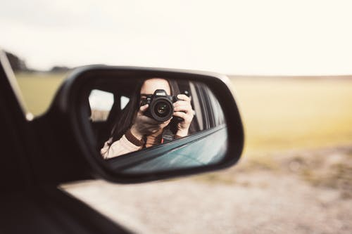 Woman with photo camera in car mirror
