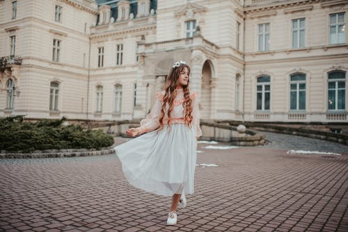Woman in White Dress Walking on Sidewalk