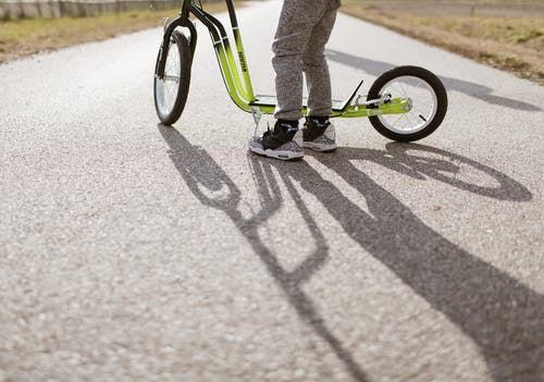 Person in Gray Pants Riding Green Bicycle on Gray Concrete Road