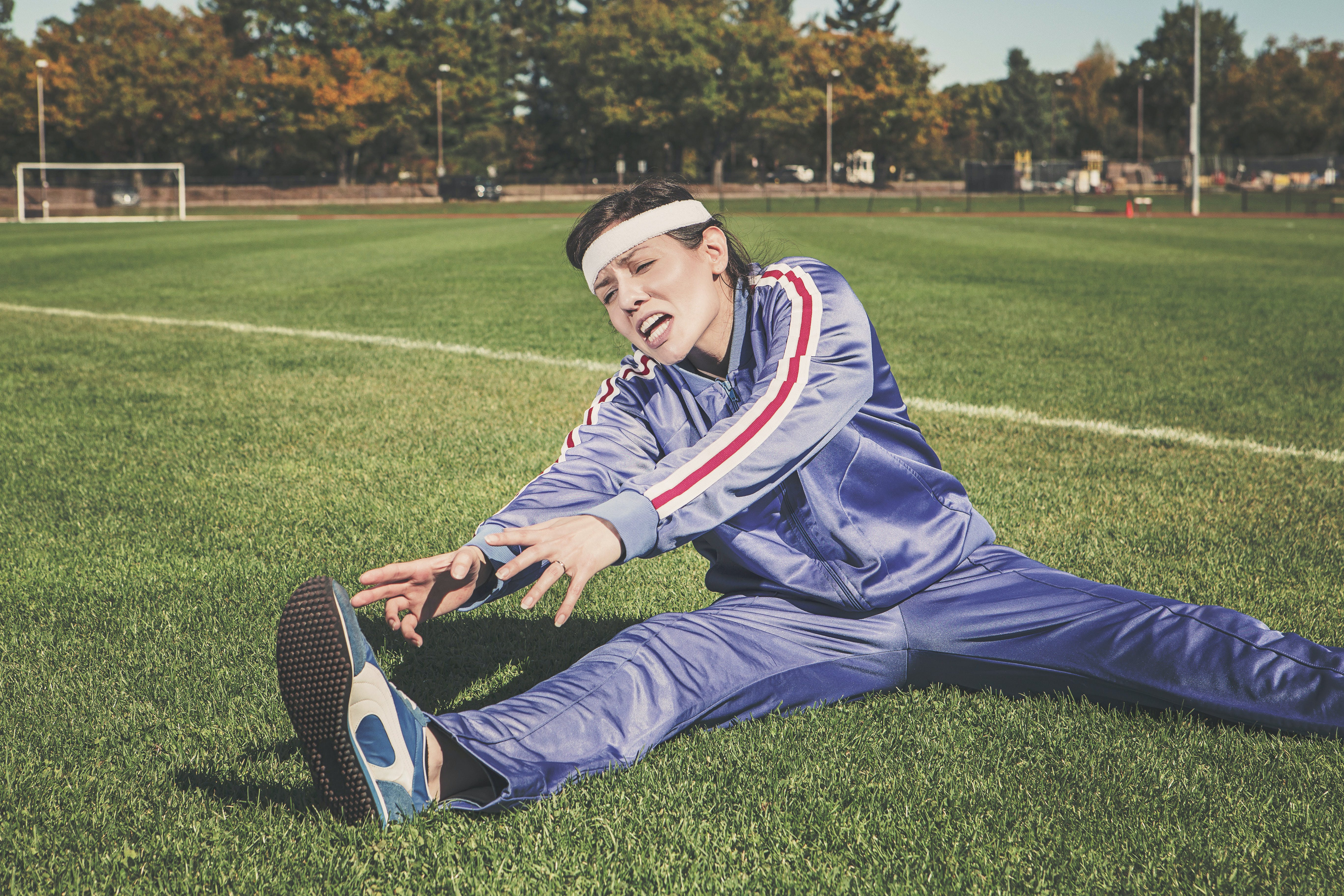 Woman Stretching on Grass Field