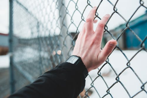 Person Wearing Black Watch Holding Gray Metal Fence
