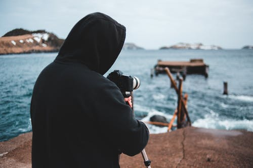Person in Black Hoodie Holding Black Dslr Camera