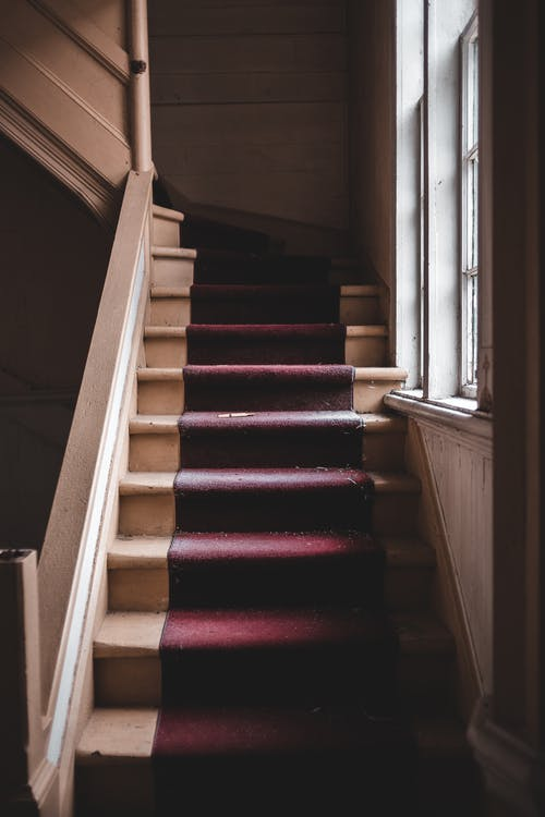 Red and Brown Staircase Near Window