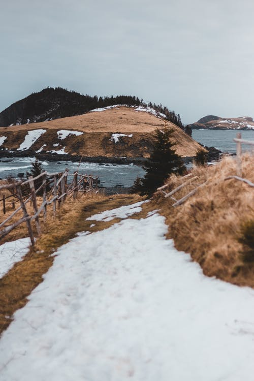 Brown Grass Field with Snow Near Body of Water