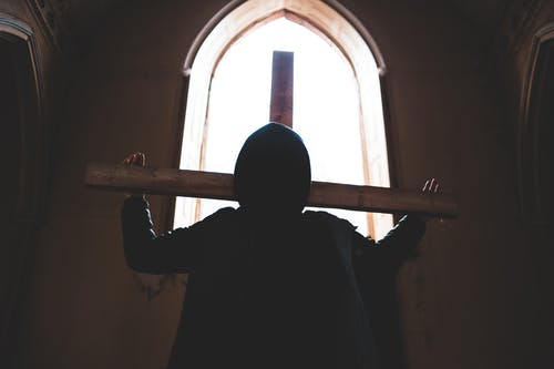 Silhouette of Man Holding a Cross Standing Near Window