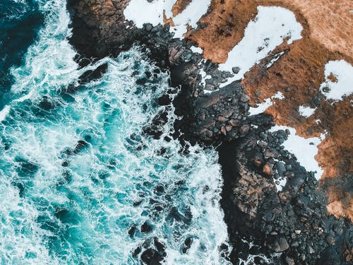 Aerial View of Ocean Waves Crashing on Rocky Shore