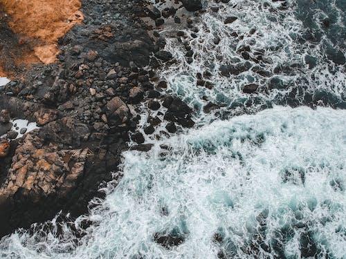 水浪击中棕色岩石