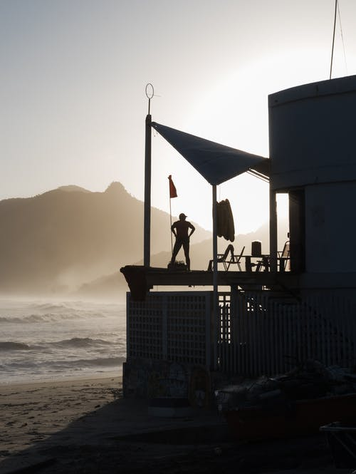 Man Standing Under Canopy Tent on Beach