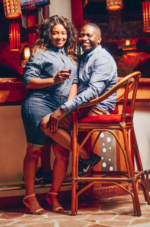 Man and Woman Sitting on Red Wooden Chair