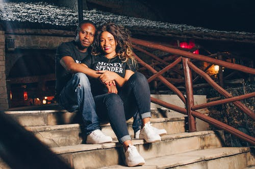 Man and Woman Sitting on Concrete Stairs