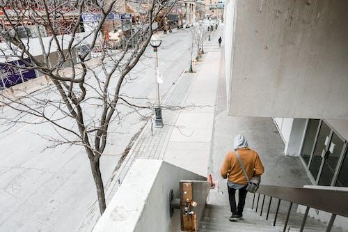 Man in Orange Jacket and Black Pants Walking Down the Stairs