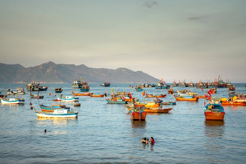 Colorful Boats on Sea Near People Swimming