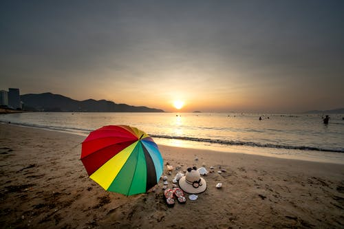 Colorful Umbrella  on Seashore During Sunset