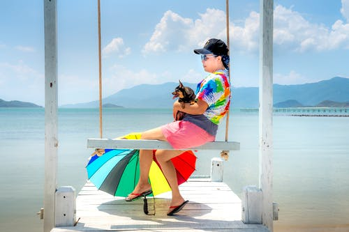 Woman Sitting on Wooden Swing Holding a Black Dog