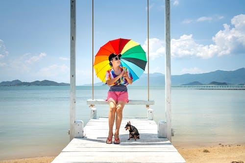Woman Holding Rainbow Umbrella Sitting on Wooden Swing