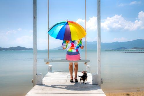 Woman Holding Umbrella Sitting on Wooden Swing