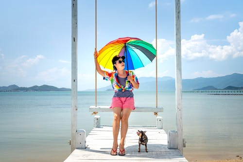Woman Sitting on Wooden Swing Holding a Rainbow Umbrella