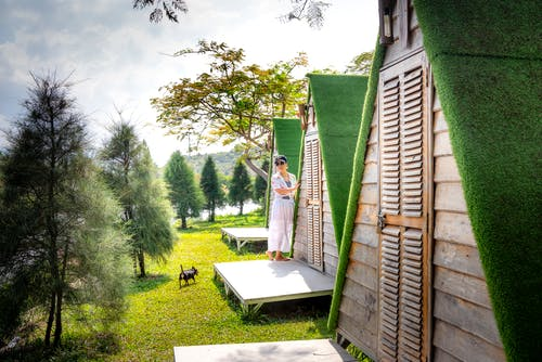 Woman standing on porch of bungalow in camping