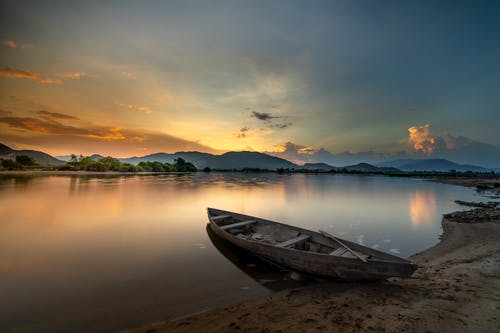White and Brown Rowboat on Shore During Sunset