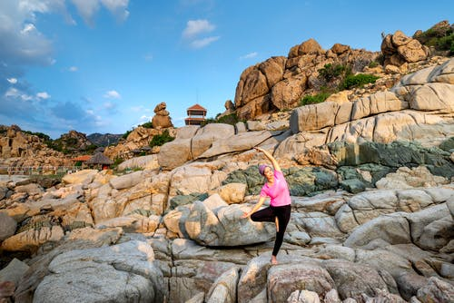 Woman in Pink Tank Top and Black Leggings Doing Yoga on Rock Formation