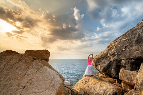 Woman in White Shirt Standing on Rock Formation Near Sea