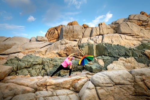 Woman in Pink Shirt and Black Pants Holding Rainbow Umbrella Standing on Rocky Mountain