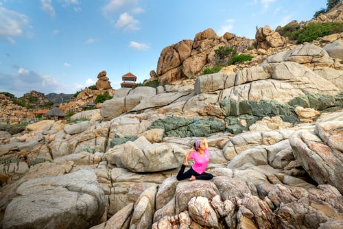 Woman in Pink Shirt and Black Pants Sitting on Brown Rock Formation
