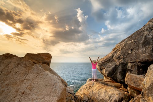 Woman in White and Blue Dress Standing on Brown Rock Formation Near Body of Water during