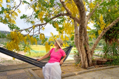 Woman in Pink Shirt and White Skirt Sitting on Black Hammock