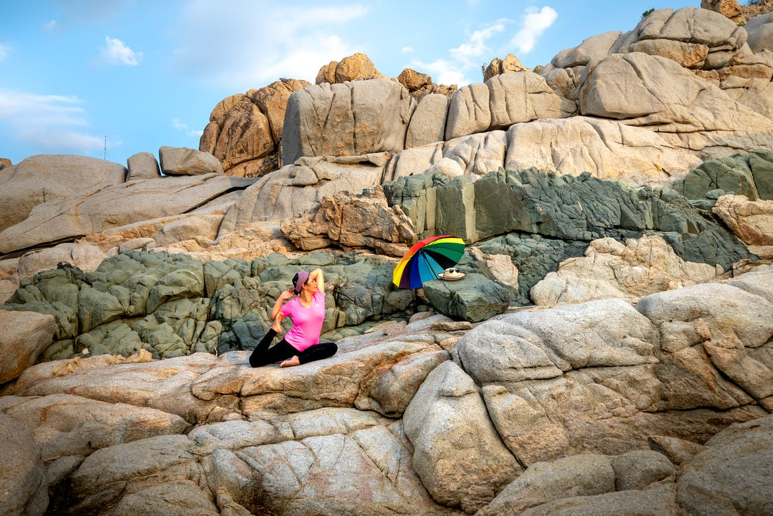 Woman in Pink Shirt Sitting on Rock