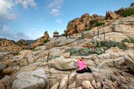 Woman in Pink Shirt and Black Pants Sitting on Rock Formation
