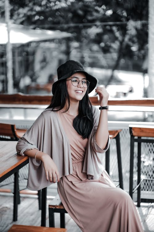 Woman in Black Bucket Hat and Pink Dress Sitting on Brown Wooden Bench